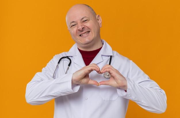 Glimlachende volwassen slavische man in doktersuniform met stethoscoop gebaren hart teken