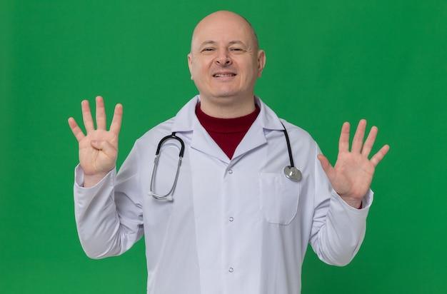 Glimlachende volwassen slavische man in doktersuniform met stethoscoop gebaren negen met vingers