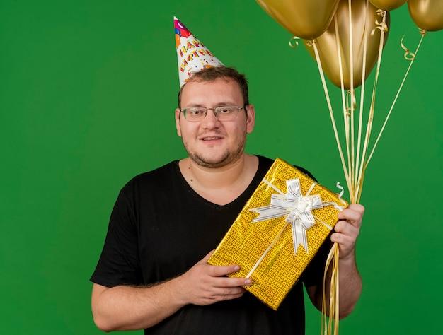 Glimlachende volwassen slavische man in optische bril met verjaardagspet houdt heliumballonnen en geschenkdoos vast