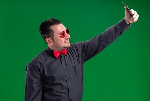 Glimlachende volwassen slavische man in rode zonnebril die selfie op telefoon neemt