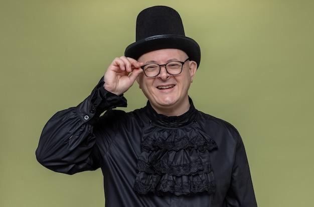 Glimlachende volwassen slavische man met hoge hoed en optische bril in zwart gotisch shirt kijkend naar de voorkant
