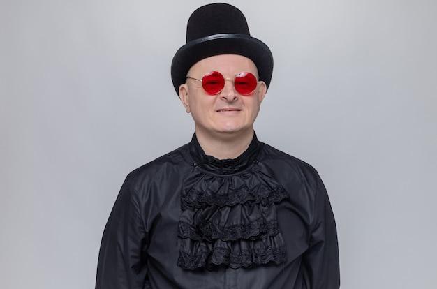 Glimlachende volwassen slavische man met hoge hoed en zonnebril in zwart gotisch shirt