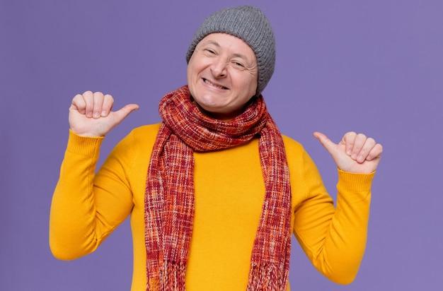 Glimlachende volwassen slavische man met wintermuts en sjaal om zijn nek wijzend naar zichzelf