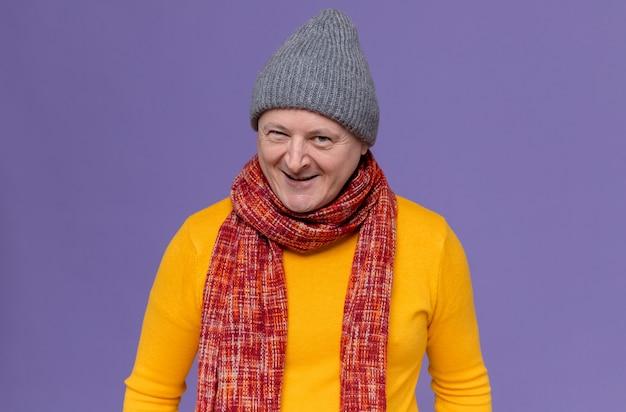 Glimlachende volwassen slavische man met wintermuts en sjaal om zijn nek