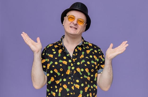 Glimlachende volwassen slavische man met zwarte hoge hoed die een zonnebril draagt die handen open houdt en kijkt
