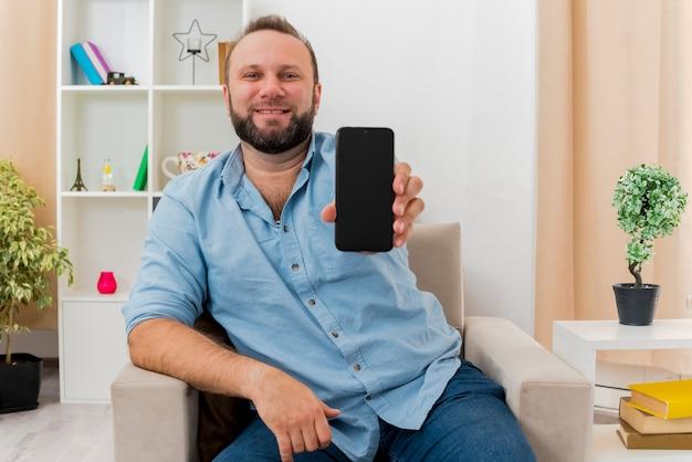 Glimlachende volwassen slavische man zit op een fauteuil met telefoon in de woonkamer