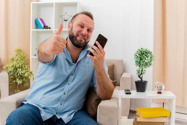 Glimlachende volwassen slavische man zit op fauteuil thumbs up houden van telefoon in de woonkamer