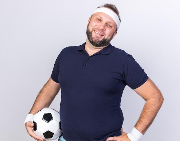 Glimlachende volwassen slavische sportieve man met hoofdband en polsbandjes met bal geïsoleerd op een witte muur met kopieerruimte