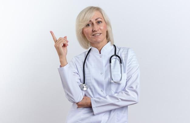 Glimlachende volwassen slavische vrouwelijke arts in medische mantel met stethoscoop omhoog geïsoleerd op een witte achtergrond met kopie ruimte