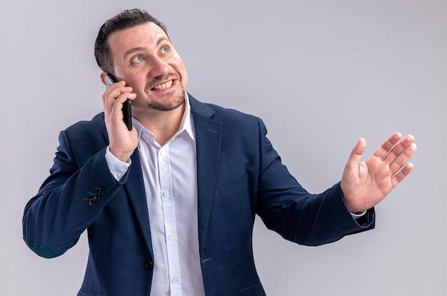 Glimlachende volwassen slavische zakenman die aan de telefoon praat en omhoog kijkt