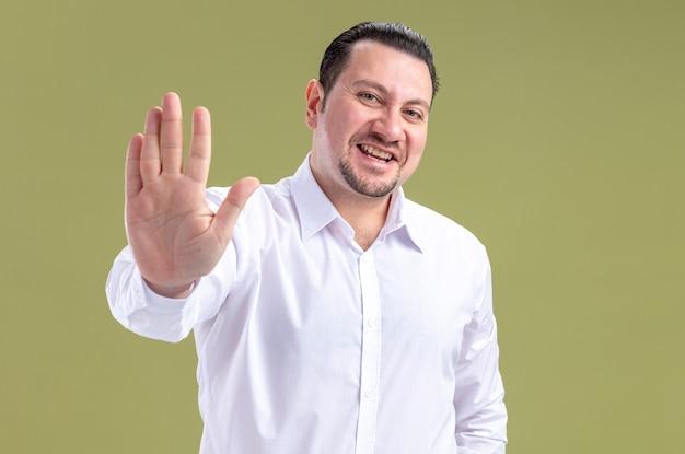 Glimlachende volwassen slavische zakenman die zijn hand open houdt