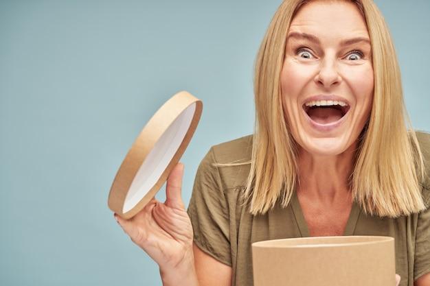 Glimlachende volwassen vrouw blij met het geschenk in de doos