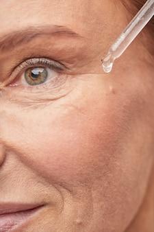 Glimlachende volwassen vrouw gebruikt moderne cosmetica
