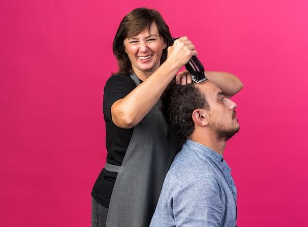 Glimlachende volwassen vrouwelijke kapper in uniform die kapsel doet voor jonge man met tondeuse geïsoleerd op roze muur met kopieerruimte