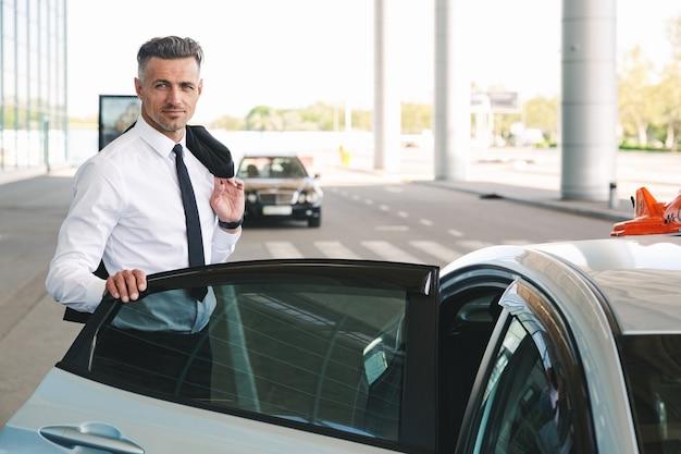 Glimlachende volwassen zakenman die in taxi buiten krijgt