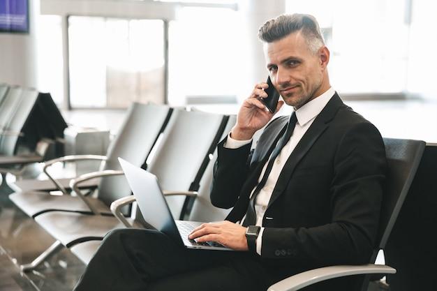 Glimlachende volwassen zakenman die op mobiele telefoon spreekt