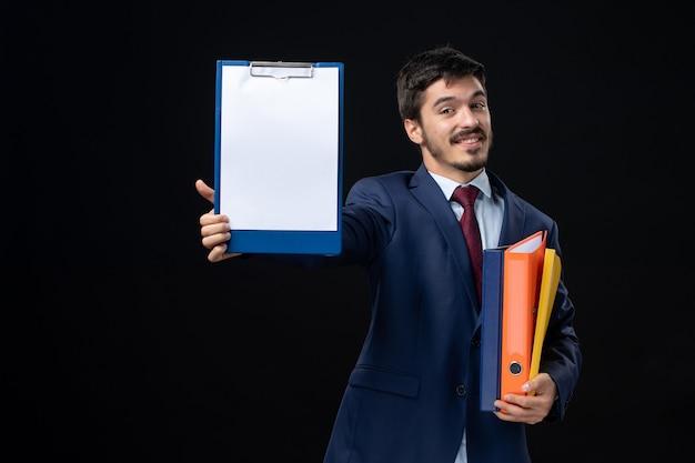 Glimlachende volwassene in pak die verschillende documenten vasthoudt en een ervan op een geïsoleerde donkere muur laat zien