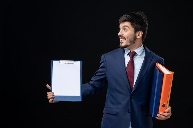 Glimlachende volwassene in pak die verschillende documenten vasthoudt en ergens aan de rechterkant op geïsoleerde donkere muur kijkt looking