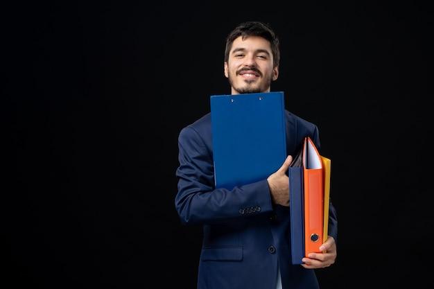 Glimlachende volwassene in pak met verschillende documenten en poseren op geïsoleerde donkere muur
