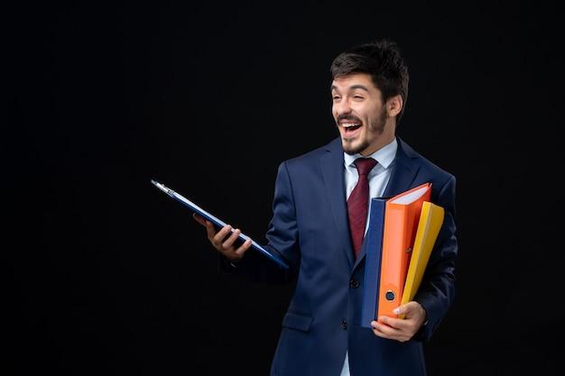 Glimlachende volwassene in pak met verschillende documenten op geïsoleerde donkere muur