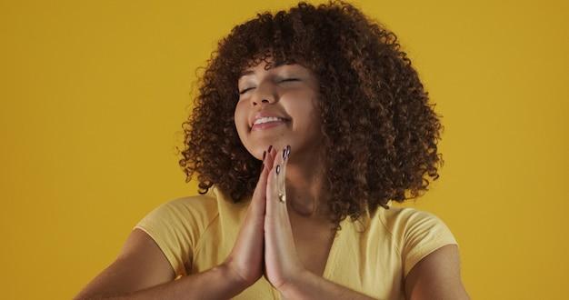 Glimlachende vreedzame jonge vrouw die yoga en meditatie beoefent. kalme vrouw die namaste-gebaar maakt en camera bekijkt. yoga-concept. dankbaarheid.