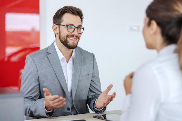 Glimlachende vriendelijke autoverkoper zit in autosalon met een vrouw die een auto wil kopen en een overeenkomst wil sluiten