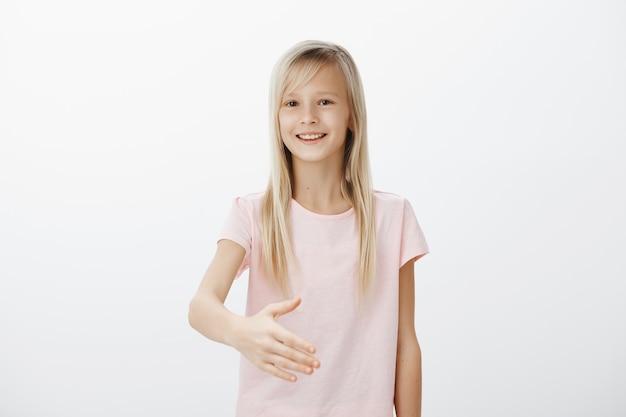 Glimlachende vriendelijke blonde vrouw strekt haar hand uit voor handdruk, leuk je te ontmoeten gebaar