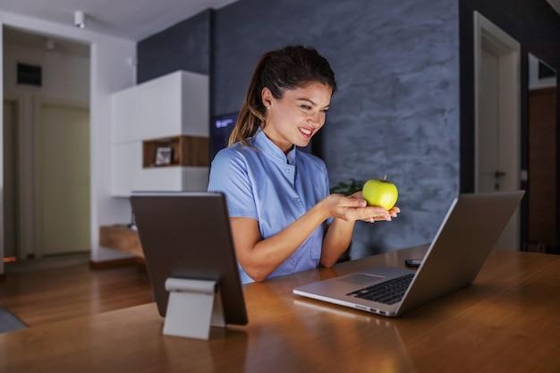 Glimlachende vriendelijke jonge verpleegster om thuis te zitten en appel te houden. via internet geeft ze adviezen voor een gezond leven.