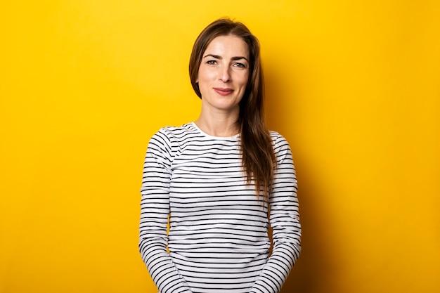 Glimlachende vriendelijke jonge vrouw in een gestreept t-shirt op geel.