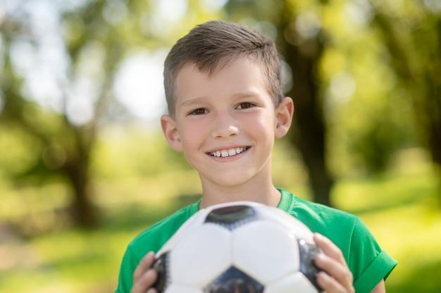 Glimlachende vriendelijke jongen met bal in handen