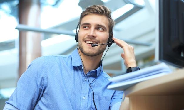 Glimlachende vriendelijke knappe jonge mannelijke callcenter-operator.
