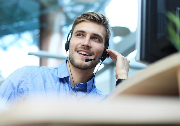 Glimlachende vriendelijke knappe jonge mannelijke callcentermedewerker