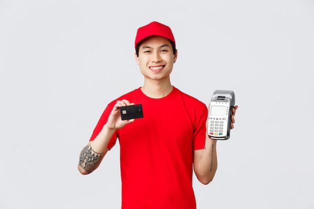 Glimlachende vriendelijke koerier in rood uniform t-shirt en pet, advies betalen voor eten bezorgen of bestellingen met creditcards met behulp van betaalterminal. bezorger toont pos-betaalmethode, staande grijze achtergrond.