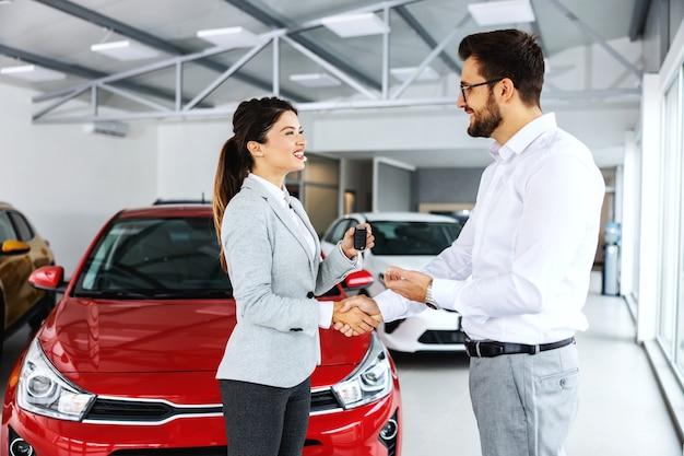 Glimlachende, vriendelijke vrouwelijke autoverkoper die zich in autosalon met een klant bevindt en hem autosleutels overhandigt