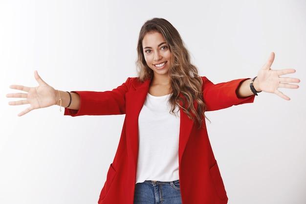 Glimlachende vriendelijke zorgeloze jonge aantrekkelijke vrouwelijke werknemer die een rood jasje draagt dat zijn handen uitstrekt zijwaarts gespreid om je te omhelzen, wil knuffelen knuffelen met steun die gelukkig grijnst, witte muur