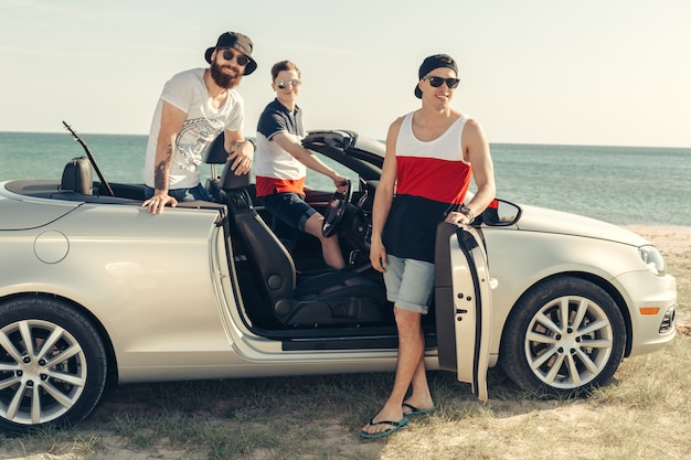 Glimlachende vrienden die auto drijven dichtbij het overzees en pret hebben