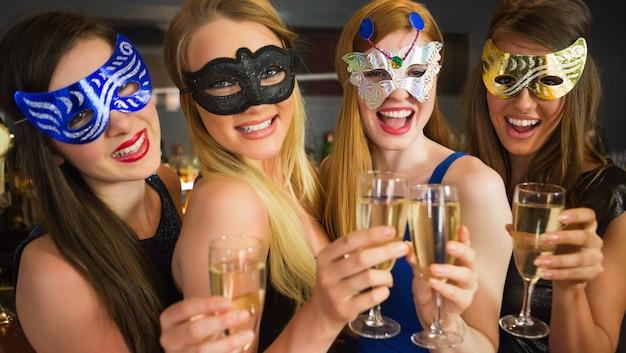 Glimlachende vrienden die champagneglazen houden die maskers dragen