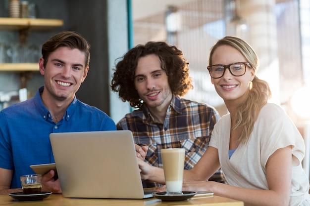 Glimlachende vrienden die digitale tablet en laptop in koffie gebruiken