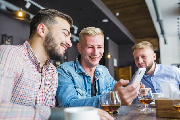 Glimlachende vrienden die in de bar zitten die mobiele telefoon bekijken