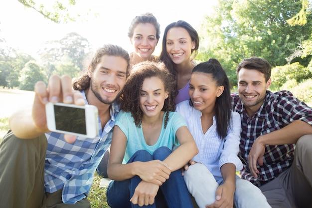Glimlachende vrienden die media apparaten in park gebruiken