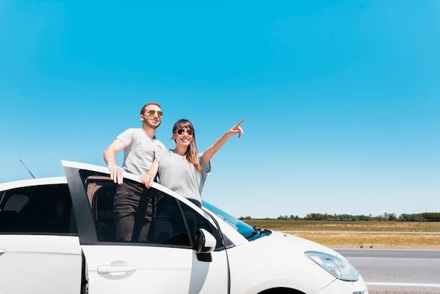 Glimlachende vrienden die op een auto zitten die op iets richten