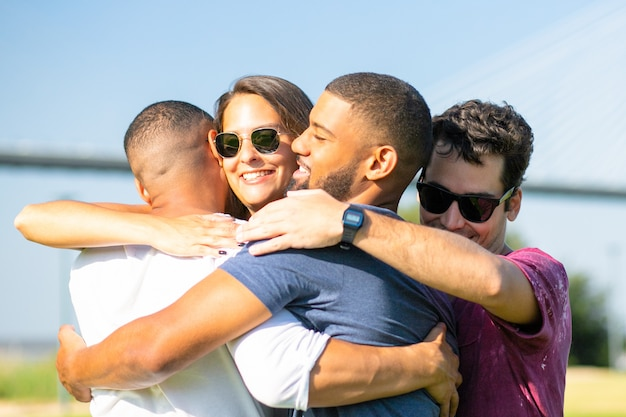 Glimlachende vrienden die op groene weide tijdens zonnige dag samenkomen. vrolijke mensen die in cirkel bij park omhelzen. unie