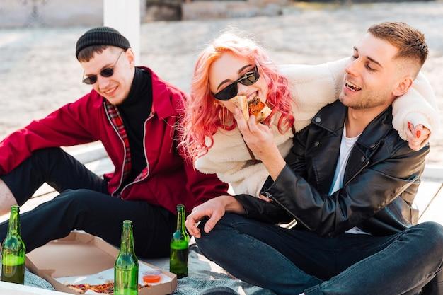 Glimlachende vrienden die pret met bier en pizza hebben in openlucht