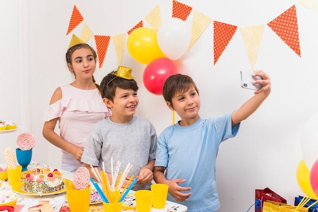 Glimlachende vrienden die selfie in mobiele telefoon nemen terwijl verjaardagspartij vieren