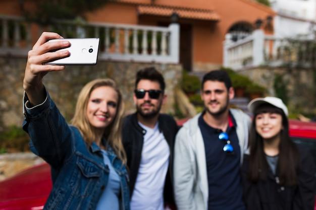Glimlachende vrienden die selfie met celtelefoon nemen