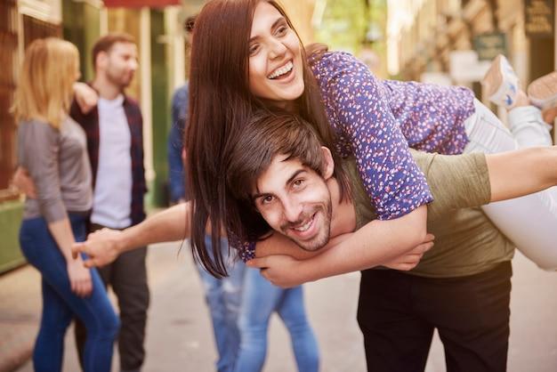 Glimlachende vrienden die van de zomer op straat genieten