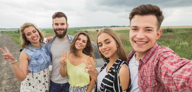 Glimlachende vrienden die zelfportret nemen in openlucht