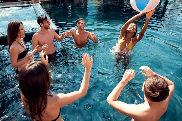 Glimlachende vrienden met plezier in zwembad