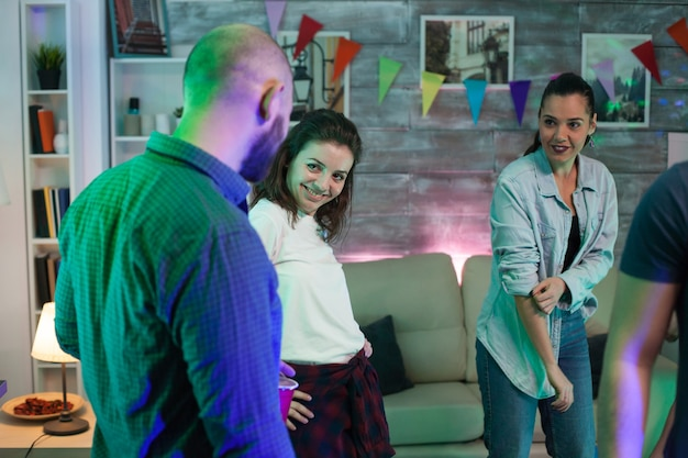 Glimlachende vriendin die naar haar vriendje kijkt terwijl ze feesten met hun vrienden.