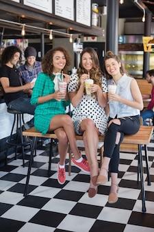 Glimlachende vriendinnen poseren met smoothies in restaurant